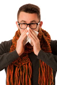 55565649 - man with flu and fever wrapped in scarf sneezing into handkerchief isolated over white.