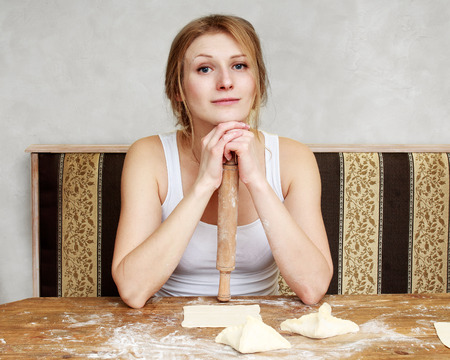 52452027 - housewife. woman is sitting on a kitchen making cookies