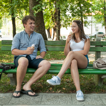 51504222 - young couple eating ice cream in shadow on a bench in park on hot summer afternoon
