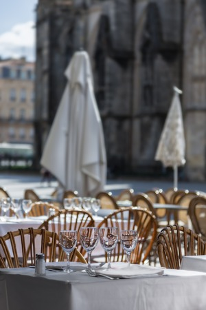 42149915 - tables outdoor cafes with wine glasses, sun umbrellas on the square of the french city, in the background gothic cathedral
