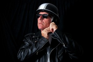 56577370 - studio shot of male biker / motorcyclist wearing vintage black leather jacket and sunglasses putting on retro helmet.
