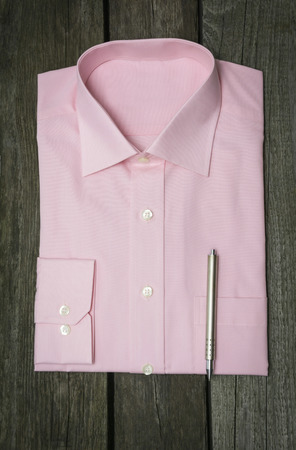 58339175 - pink shirt and mobile on wooden background