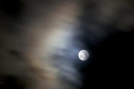 51268480 - a 8 second exposure of a full bright moon on an autumn night with fast moving clouds creating blur.